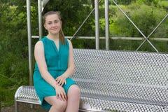 Adolescente en banco en parque Fotos de archivo libres de regalías