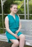 Adolescente en banco en parque Imágenes de archivo libres de regalías