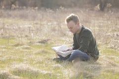 Adolescente en biblia abierta de la lectura del campo Imagen de archivo