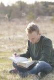 Adolescente en biblia abierta de la lectura del campo Foto de archivo libre de regalías