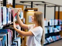 Adolescente en biblioteca Fotografía de archivo libre de regalías