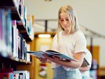 Adolescente en biblioteca Imagenes de archivo