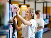 Adolescente en biblioteca Fotos de archivo libres de regalías