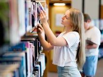 Adolescente en biblioteca Imagen de archivo libre de regalías
