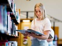 Adolescente en biblioteca Fotos de archivo
