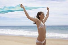 Adolescente en bikini con las manos aumentadas sosteniendo la bufanda en la playa Foto de archivo libre de regalías