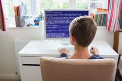 Adolescente en código de ordenador de la escritura del dormitorio Imagenes de archivo