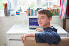 Adolescente en código de ordenador de la escritura del dormitorio Foto de archivo libre de regalías