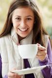 Adolescente en café al aire libre con la bebida caliente Fotos de archivo