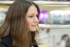 Adolescente en café que bebe el zumo de naranja, centro de entretenimiento de la alameda de compras del fondo Imagenes de archivo