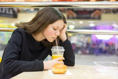 Adolescente en café que come la torta y el zumo de naranja Foto de archivo libre de regalías