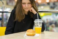 Adolescente en café que come la torta y el zumo de naranja Céntrese en la torta, centro de entretenimiento de la alameda de compr Imagenes de archivo