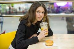 Adolescente en café que come la torta y el zumo de naranja, centro de entretenimiento de la alameda de compras del fondo Imágenes de archivo libres de regalías