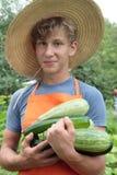 Adolescente en calabacín de la explotación agrícola del sombrero de paja Imágenes de archivo libres de regalías