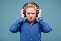Adolescente en camisa y auriculares azules Imagen de archivo