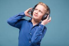 Adolescente en camisa y auriculares azules Fotografía de archivo