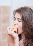 Adolescente en camiseta anaranjada que come un melocotón Foto de archivo libre de regalías
