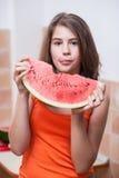 Adolescente en camiseta anaranjada que goza comiendo una rebanada de sandía Fotografía de archivo