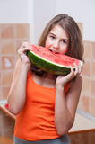 Adolescente en camiseta anaranjada que goza comiendo una rebanada de sandía Fotos de archivo libres de regalías