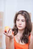 Adolescente en camiseta anaranjada que piensa y que sostiene un melocotón en su mano Foto de archivo libre de regalías