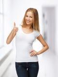 Adolescente en camiseta blanca en blanco con los pulgares para arriba Imagen de archivo libre de regalías