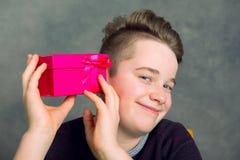 Adolescente en camiseta marrón con la caja de regalo roja Foto de archivo libre de regalías