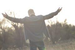 Adolescente en campo abierto con los brazos aumentados Imagen de archivo libre de regalías