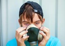 Adolescente en careta antigás Imagenes de archivo