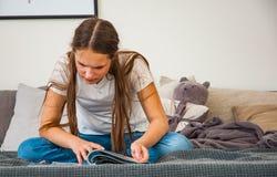 Adolescente en casa que se sienta en el sofá, leyendo una revista Imágenes de archivo libres de regalías