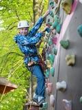 Adolescente en casco y con una pared que sube de la cuerda de la seguridad que sostiene los ganchos Fotografía de archivo