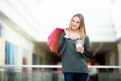 Adolescente en centro comercial con las bolsas de papel y la fresa c Imagen de archivo
