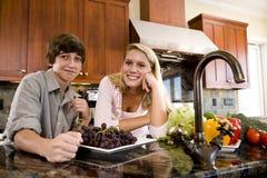 Adolescente en cocina con el hermano menor Imagen de archivo libre de regalías