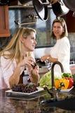 Adolescente en cocina que charla con la madre Imagen de archivo