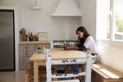 Adolescente en cocina usando el ordenador portátil y el teléfono, vista lateral Fotografía de archivo