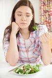 Adolescente en dieta que come la placa de la ensalada Imagenes de archivo