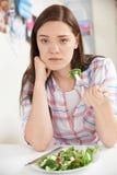 Adolescente en dieta que come la placa de la ensalada Imágenes de archivo libres de regalías
