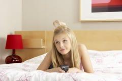 Adolescente en dormitorio con el teléfono móvil Imagen de archivo