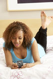 Adolescente en dormitorio con el teléfono móvil Fotografía de archivo libre de regalías