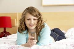 Adolescente en dormitorio con el teléfono móvil Fotos de archivo