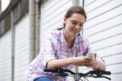Adolescente en el ambiente urbano usando el teléfono móvil mientras que monta B Imagen de archivo libre de regalías