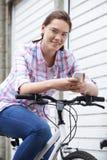Adolescente en el ambiente urbano usando el teléfono móvil mientras que monta B Foto de archivo libre de regalías