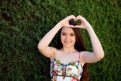 Adolescente en el amor que hace un corazón con su mano Imágenes de archivo libres de regalías
