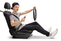 Adolescente en el asiento de carro que lleva a cabo llave del volante y del coche Foto de archivo