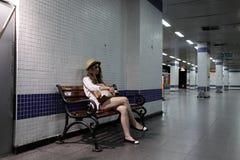 Adolescente en el banco en la estación de metro Imágenes de archivo libres de regalías