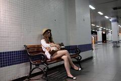 Adolescente en el banco en la plataforma del subterráneo Foto de archivo