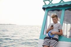 Adolescente en el barco usando el smartphone, océano en la distancia Imagenes de archivo