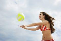 Adolescente en el bikini que juega a voleibol de playa Foto de archivo libre de regalías