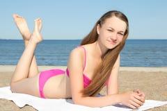 Adolescente en el bikini rosado que miente en la playa Fotografía de archivo libre de regalías