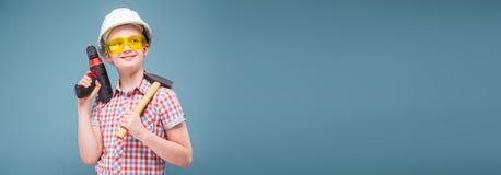 Adolescente en el casco de la construcción con un martillo y un destornillador Foto de archivo