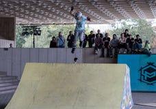 Adolescente en el casco que hace trucos en pcteres de ruedas en una rampa Imagen de archivo libre de regalías